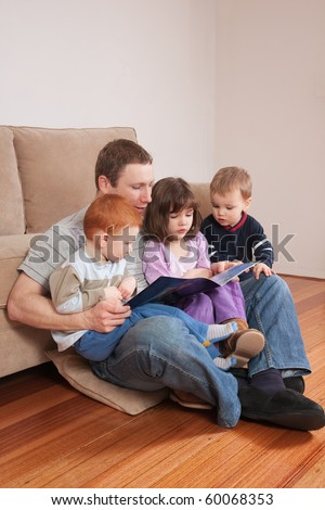 Father reading story to three kids sitting on his lap