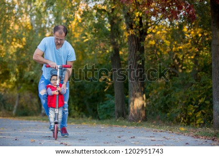 Father riding with his toddler son  scooter in a autumn park. . Active family leisure. Sports, leisure with kids concept.