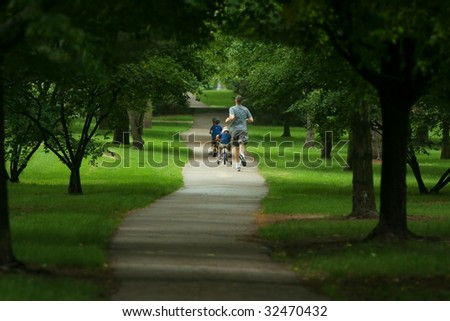 father running and sons biking in park on paved path