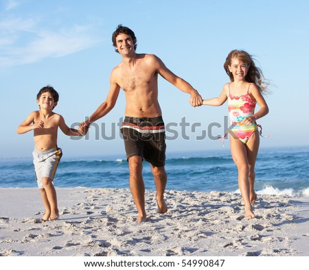 Father Running With Children Along Sandy Beach - stock photo