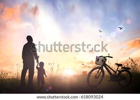 Father's Day concept: Silhouette child's hand holding father's finger with bicycle on meadow sunset background #658093024