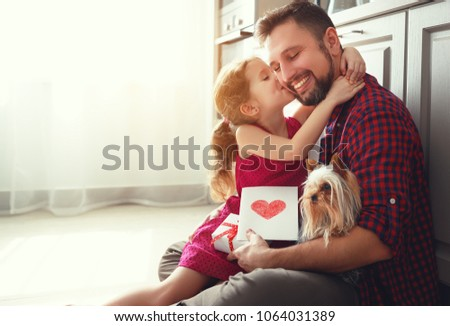 Father's day. Happy family daughter giving dad a greeting card on holiday