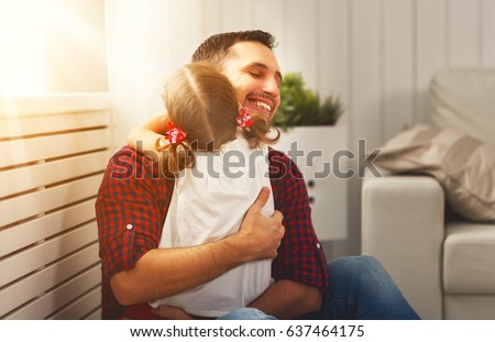 Shutterstock Father's day. Happy family daughter hugging dad and laughs on holiday