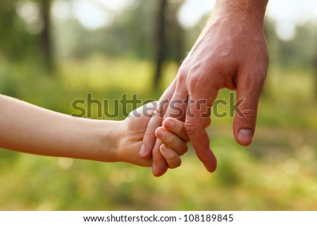 father's hand lead his child son in summer forest nature outdoor, trust family concept
