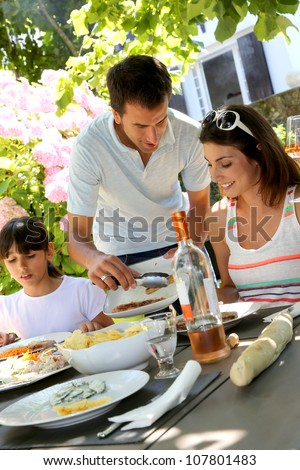 Father serving grilled meat to family - stock photo