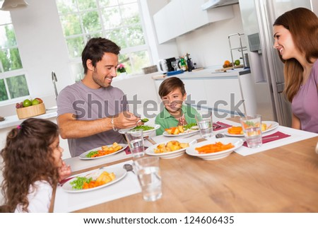 Father serving vegetables to son in kitchen