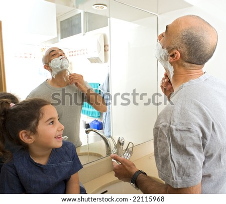 father shaving and little daughter watching in bathroom