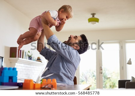 Father Sits At Table And Plays With Baby Son At Home #568485778