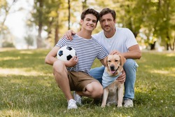 father sitting on grass near pleased teenager son with football and golden retriever