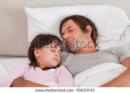 Father sleeping with his daughter in a bedroom