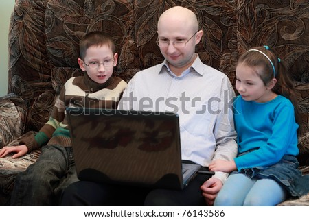 Father, son and daughter sitting on couch and look at laptop screen