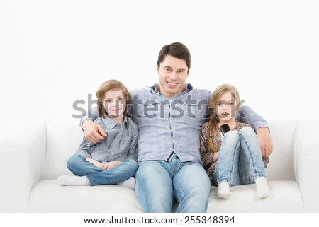 Father son and daughter watching television sitting on the couch on a white background