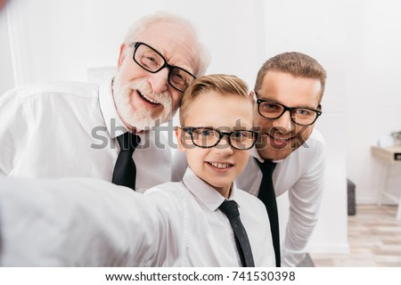 Father, son and grandfather wearing formal clothing and glasses taking a selfie