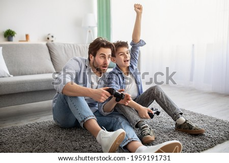 Father-son competition. Joyful boy winning dad in videogame and raising hand, celebrating victory. Family having fun at home, sitting on floor carpet, empty space