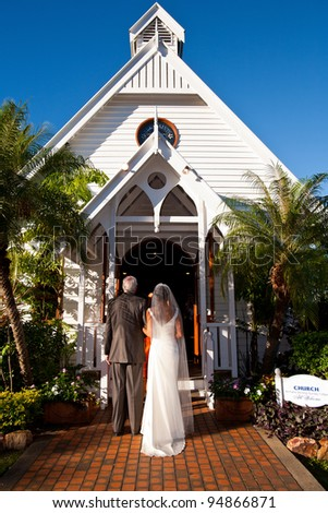 Father standing with bride outside a church, ready to give her away