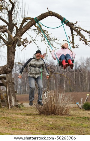 Father swinging daughter in a garden. Fun in early spring.