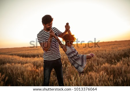 Father swinging his daughter in the field