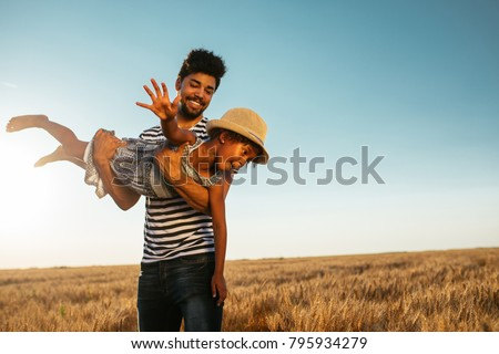 Father swinging his daughter in the field #795934279