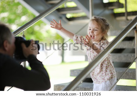 Father taking picture of smiling young girl outdoors