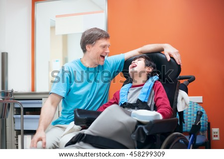 Father talking with disabled biracial son sitting in wheelchair while waiting in doctor\'s office, laughing together.