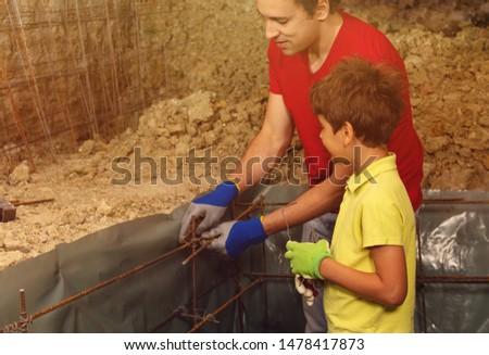 Father teaches boy prepare framework for concrete