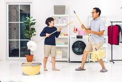 Father teaching asian kid little boy son having fun doing household chores cleaning and washing floor wiping dust with mopping and vacuum cleaner while cleaning house together at home