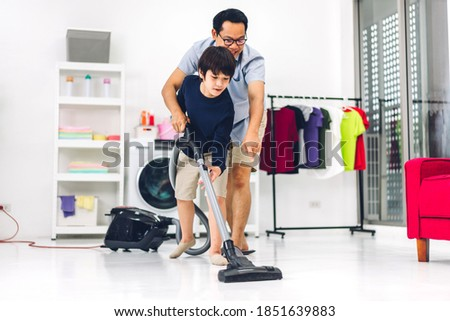 Father teaching asian kid little boy son having fun doing household chores cleaning and washing floor wiping dust with vacuum cleaner while cleaning house together at home.Housework concept Stock photo ©