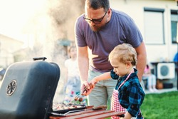 Father teaching his little son how to grill while standing in backyard at summer. Family gathering concept.