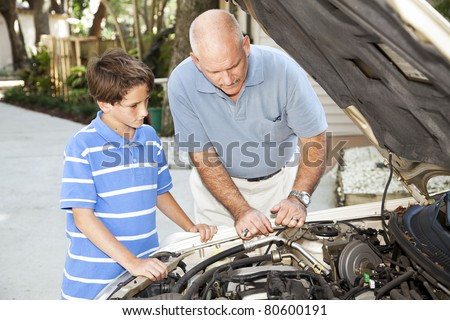 Father teaching his son how to repair the car.