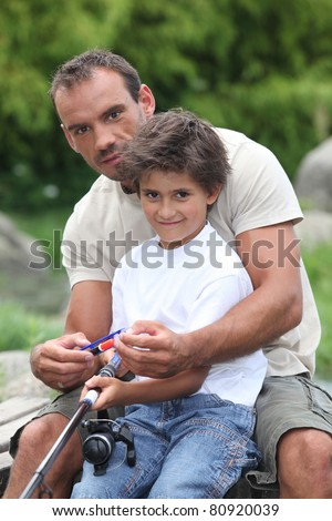 Father teaching his son to fish