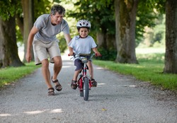 Father teaching his son to ride a bike