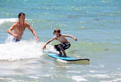 Father teaching his young son how to surf in shallow sea on vacation