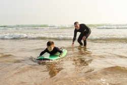 Father teaching son surfing in ocean. Happy father helping little son in wetsuit lying and swimming on surfboard on waves. Surfing concept