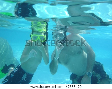 Father teaching son underwater safety hand signals for SCUBA diving