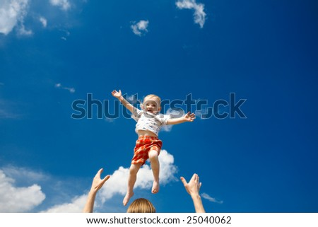 father throw his daughter over blue sky
