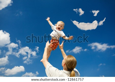 father throw his daughter over blue sky and clouds smile