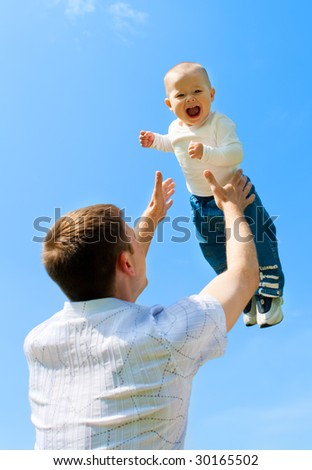 Father throwing baby boy against blue sky