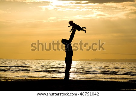 Father throwing his kid up in the air on the beach