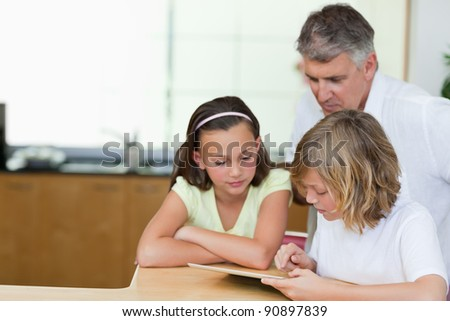 Father together with his children and tablet in the kitchen