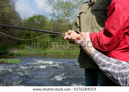father together with his sons fishing on the mount river, hands close up #1076284019