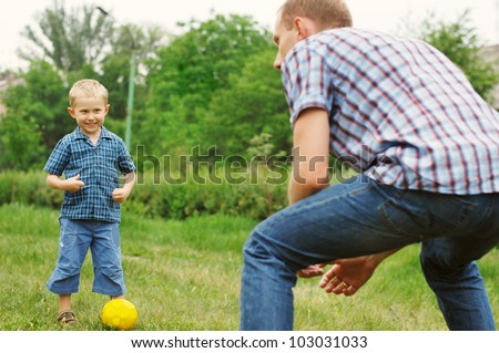 Father training his little son play in football