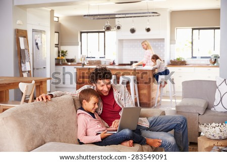 Father using computer with son, family in background