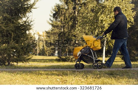 Father walking with baby stroller in fall park  #323681726