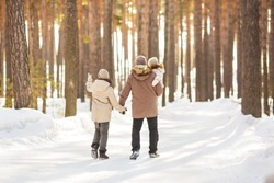 Father walks with his little daughters and teen-son in a forest in winter