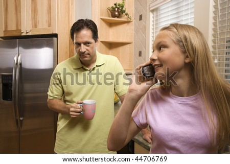 Father watching daughter talk on cell phone while in kitchen
