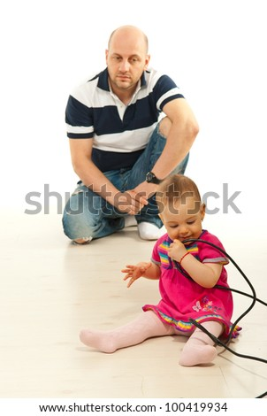 Father watching his baby girl playing with cables on floor
