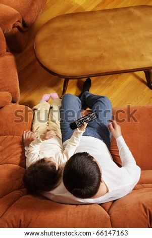 Father watching television with daughter above view