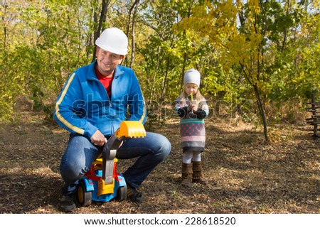 Father wearing a hardhat riding on his childs colorful plastic toy front end loader watched anxiously by a cute anxious little girl with her hands clasped