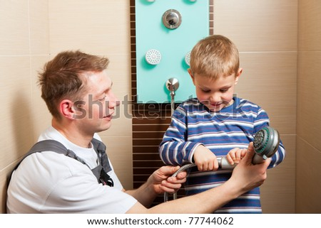 Father, who is a Plumber, installing a mixer tap in a bathroom; explaining what he does to his son