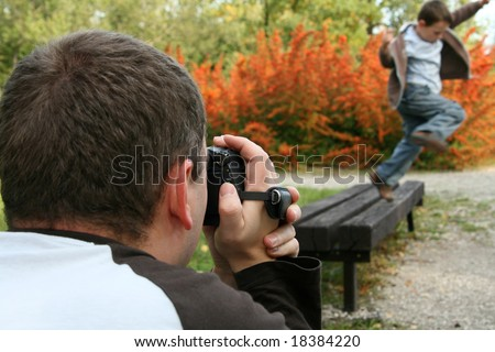 Father with a digital video camera recording his son.